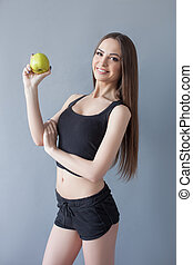 Cheerful young woman is eating healthy food