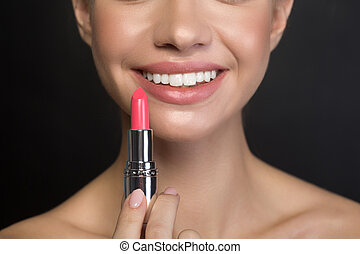 Cheerful young woman is enjoying using make-up products
