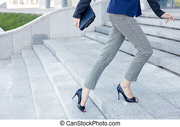 Cheerful young woman is going to work - Close up of legs of...