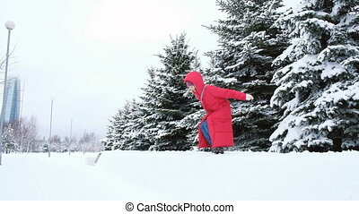 Cheerful young woman jumping in the snow from the curb.