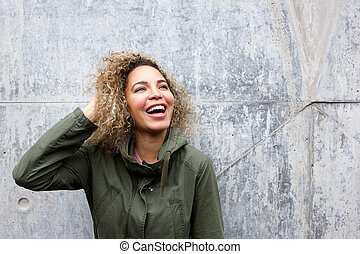 Cheerful young woman laughing with hand in hair