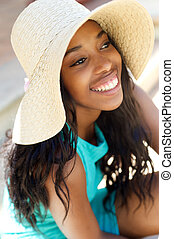 Cheerful young woman laughing with sun hat