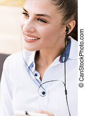 Cheerful young woman listening music on smartphone outdoor