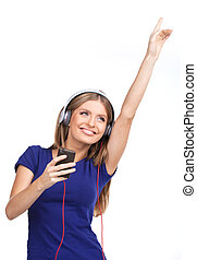 Cheerful young woman listening music with headphones. pretty brunette standing on white background and lifting hands
