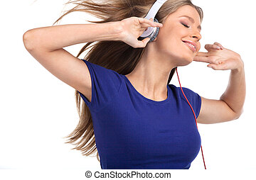Cheerful young woman listening music with headphones. side view of pretty brunette standing on white background and holding headphones