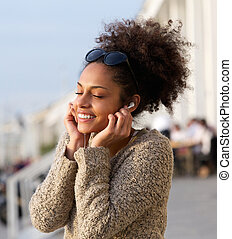 Cheerful young woman listening to music outdoors