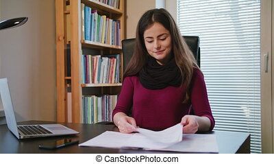 Cheerful Young Woman Looking on Documents.