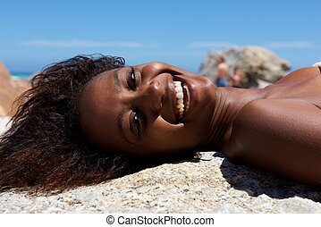 Cheerful young woman lying outdoors