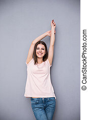 Cheerful young woman over gray background