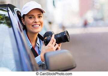 young woman photographing from a car