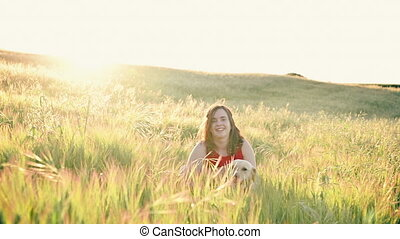 Cheerful young woman playing with her dog on the meadow at ...