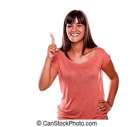 Cheerful young woman pointing up looking at you