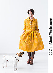 Cheerful young woman posing in a yellow dress with her beloved dog Jack Russell Terrier standing on a white background. The concept of casual wear and pets