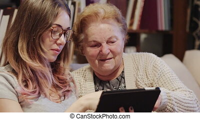 Cheerful young woman showing her grandmother how to use a tablet