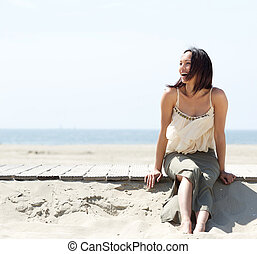 Cheerful young woman sitting by the beach