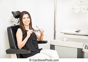 Cheerful young woman sitting in patient chair in ophthalmologic clinic holding frame