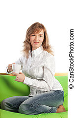 Cheerful young woman sitting on sofa