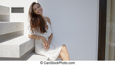 Cheerful young woman sitting on stairs