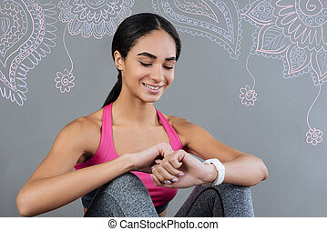 Cheerful young woman smiling while looking at her convenient watch
