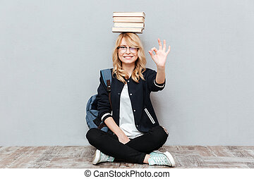 Cheerful young woman student holding books on head.