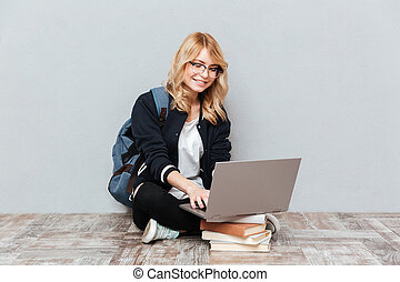 Cheerful young woman student using laptop computer.