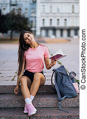 Cheerful young woman taking notes while sitting on steps on the street