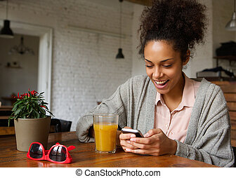 Cheerful young woman typing a text message on mobile phone