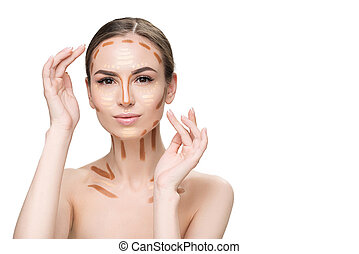 Cheerful young woman using concealers - Thoughtful girl is...