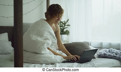Cheerful young woman using her laptop computer sitting in bed at home