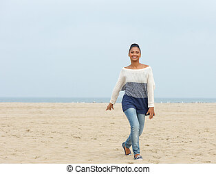 Cheerful young woman walking on a beach
