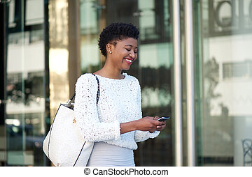 Cheerful young woman walking with cellphone