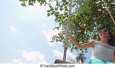 Cheerful young woman wearing sunglasses relaxes on the swing in slow motion with beautiful sun flare effect. 1920x1080