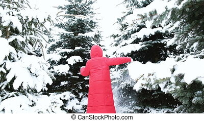 Cheerful young woman whirls in a snowy forest and falls to...