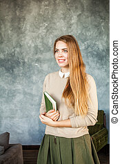 Cheerful Young Woman with Book at Home