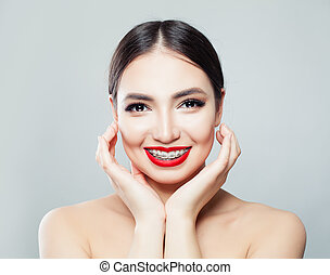 Cheerful young woman with braces on teeth laughing and touching her face by hand over white background