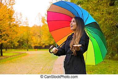Cheerful young woman with colorful umbrella checking for rain in city park.