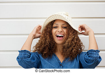 Cheerful young woman with hate laughing outdoors