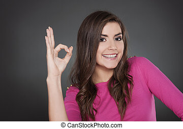 Cheerful young woman with OK sign