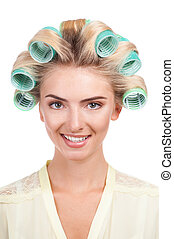 Cheerful young woman with rollers in her head