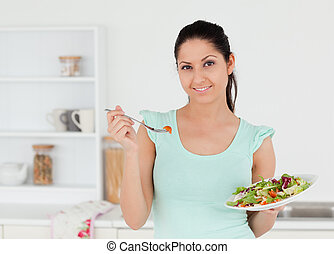 Cheerful young woman with salad