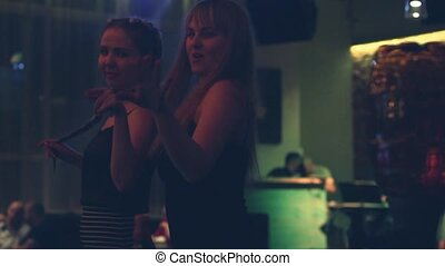 cheerful young women dancing and singing at a birthday party