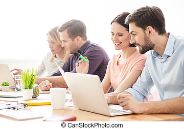 Cheerful young workers are talking in office