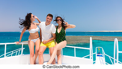 Cheerful youth laughing and standing on the yacht at a sunny...