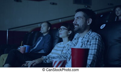 Cheerful youth men and women watching film in movie theater ...