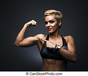 Cheerfully smiling sporty woman demonstrating biceps