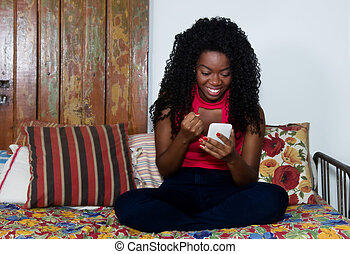 Cheering african american woman with phone