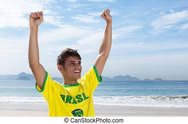 Cheering brazilian sports fan at beach