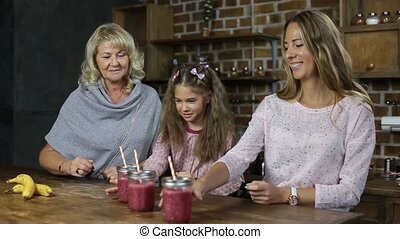 Cheering family with mason jars of smoothie - Portrait of...