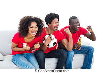 Cheering football fans in red sitting on couch