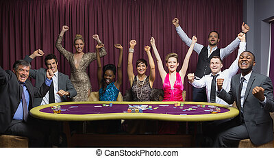 Cheering group at poker table in casino